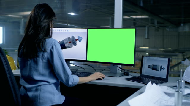 Professional Female Engineer Designs 3D Turbine/ Engine For a Big Industrial Company, Her Second Monitor Shows Mock-up Green Screen Computer. Out of the Office Window Big Factory is Seen. video