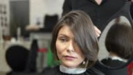 Professional Hair Dresser using a mirror to show his haircut to a client. Young woman getting her hair dressed in salon. video