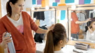 Professional hairdresser doing hairstyle for beautiful girl. video