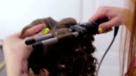 Professional hairdresser doing hairstyle for pretty teen girl - making curls video