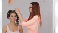 Professional hairdresser doing hairstyle for young pretty woman video