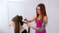 Professional hairdresser doing hairstyle for young pretty woman - making curls video