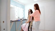 Professional hairdresser doing hairstyle for young pretty woman with long hair video