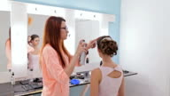 Professional hairdresser using hair spray in white make up room video