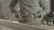 Professional locksmith make marks on wooden board by special ruler. Furniture video