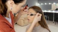 Professional makeup artist applies makeup to a beautiful model. Colors eye video