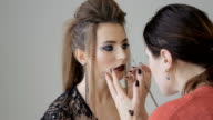Professional makeup artist applies makeup to a beautiful model. Colors of red lipstick. Close-up video