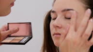 Professional make-up artist applying cream base eyeshadow primer to model eye video