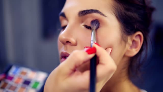 Professional make-up artist applying eyeshadow to model eye using special brush. Beauty, makeup and fashion concept. Slowmotion shot video