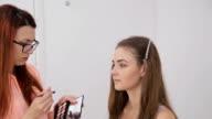 Professional make-up artist applying eyeshadow video