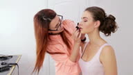 Professional make-up artist applying lipstick on lips of client video