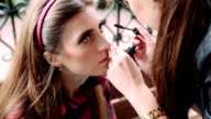 Professional makeup artist applying make up on a beautiful young female model's face outdoor video