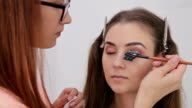 Professional make-up artist combing eyelashes of model video