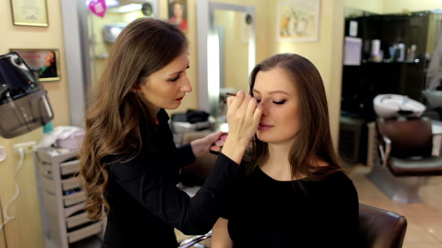 Professional make-up artist doing make-up for girl video