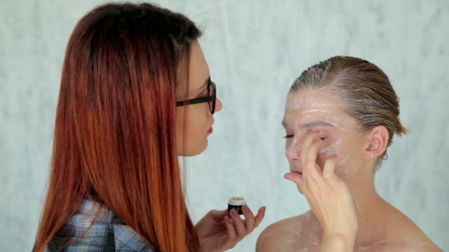 Professional make-up artist making face art in white room video