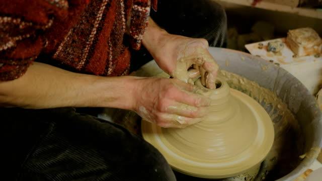 Professional male potter making ceramics in workshop video