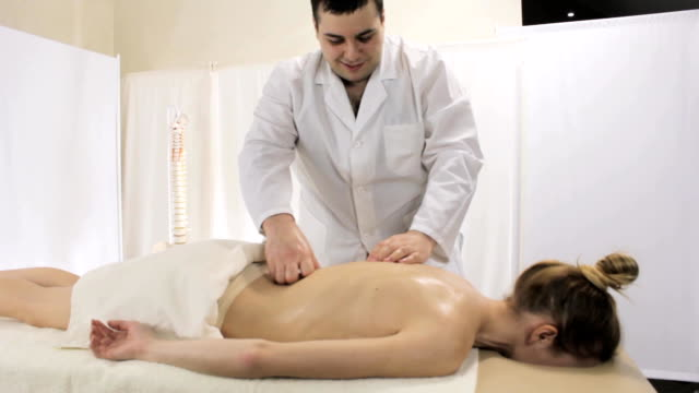 Professional masseur doing healing massage clinic of the lower spine of a young woman video