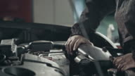 Professional mechanic repairing a car in auto repair shop video