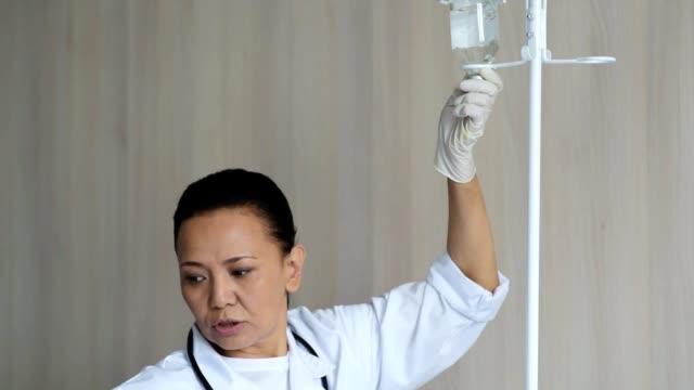Professional nurse adjusting a dropper video
