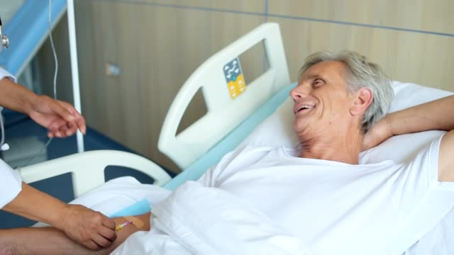 Professional nurse getting an aged man on a drip video