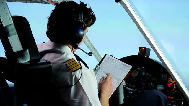 Professional pilot filling out flight papers while flying airplane, profession video