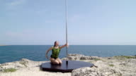 Professional pole dancer during outdoor extreme fitness workout video