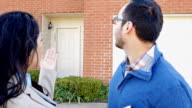Professional real estate agent showing suburban home to Hispanic male home buyer video