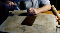 A professional re-enactment craftsman making leather item video