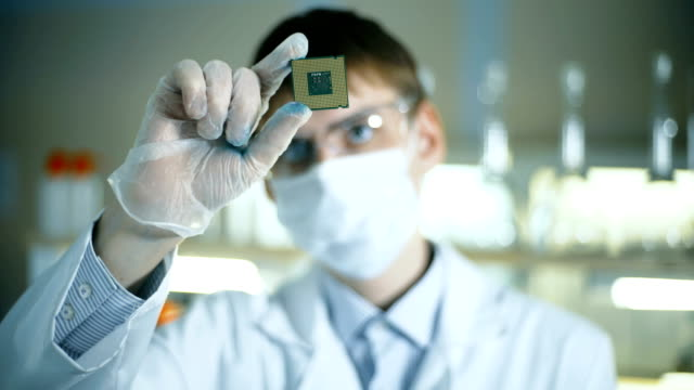 Professional scientist holding and observing the micro chip. video