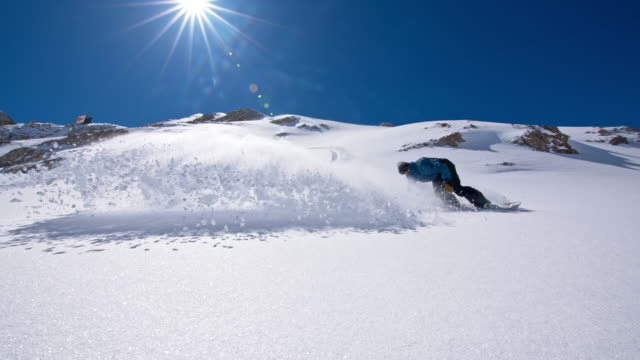 SLO MO Professional snowboarder carving and spraying snow video