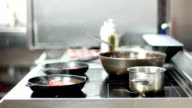 Professional stove stands in the kitchen of the restaurant, the food in the pots and pans are preparing, professional cookware made of iron video
