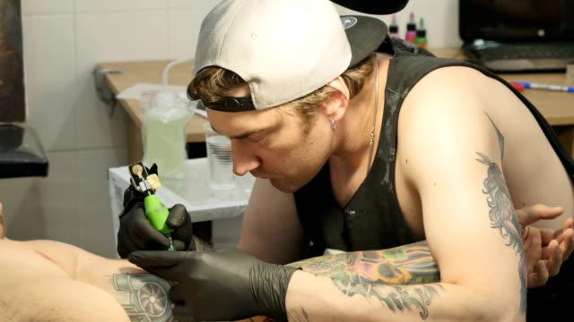 Professional tattoo artist is making the tattoo on man's hand video