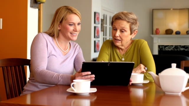 Professional Uses Digital Tablet with Senior Woman video