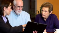 Professional Woman Interacts with Senior Couple using Digital Tablet video