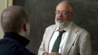 Professor and student talking in a classroom video