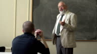Professor and student talking in a classroom, wide shot video
