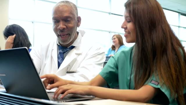 Professor encouraging nursing or medical student in college classroom video