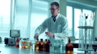 Professor pouring agent to test tube video