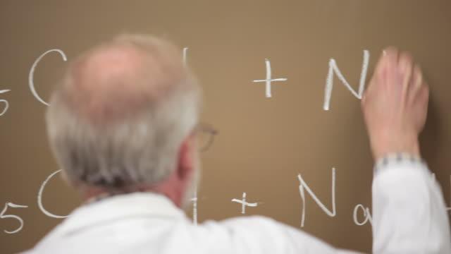 Professor writes on chalk board video