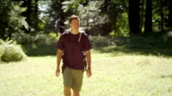 Profile of fit and healthy man hiking through park video