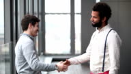 Profile of two advertising executives shaking hands video
