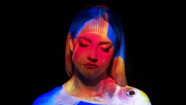 Projection of a goldfish on a woman's face video
