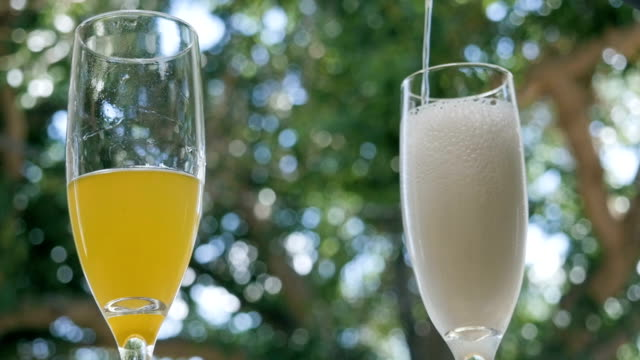 Prosecco Pours into a Champagne Flute at an Outdoor Bar to Make Mimosas video