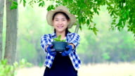 Protect the nature - Teenager girl holding a potted plant in a garden video