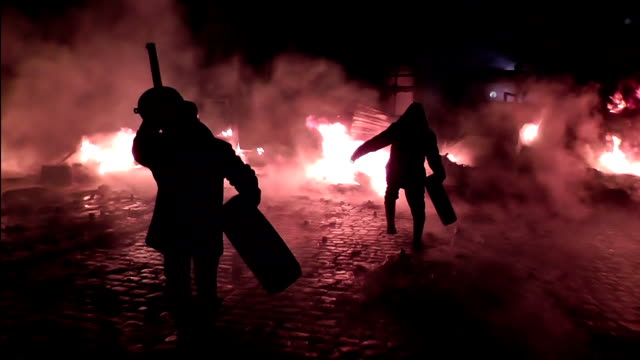 Protesters throw automobile tires in the fire. video