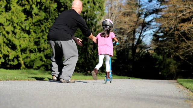 Proud Dad Helps Daughter Ride Scooter-With Helmut video