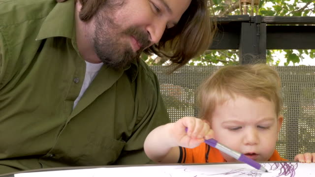 A proud father watches his baby boy coloring with a marker in slow motion video
