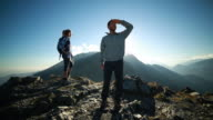 Proud hikers standing on mountain peek at sunset video
