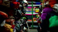 Pull focus on shelves racked with many colorful fabrics video