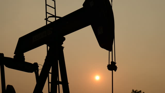 pumpjack at an oil drilling site and sunset video